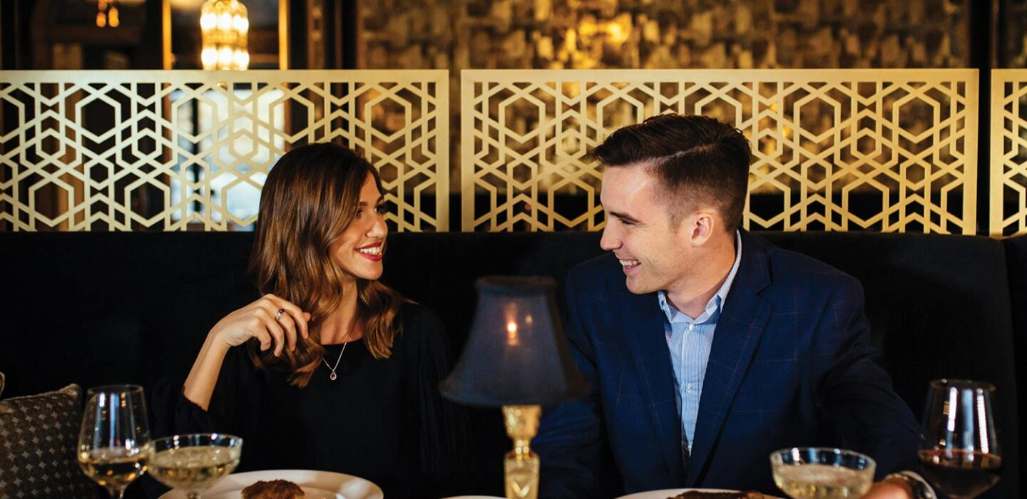 man and woman smiling at each other at a restaurant table