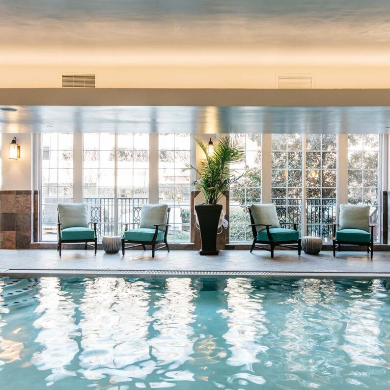 indoor pool with a large window on one side with pool chairs and potted plants in front of it