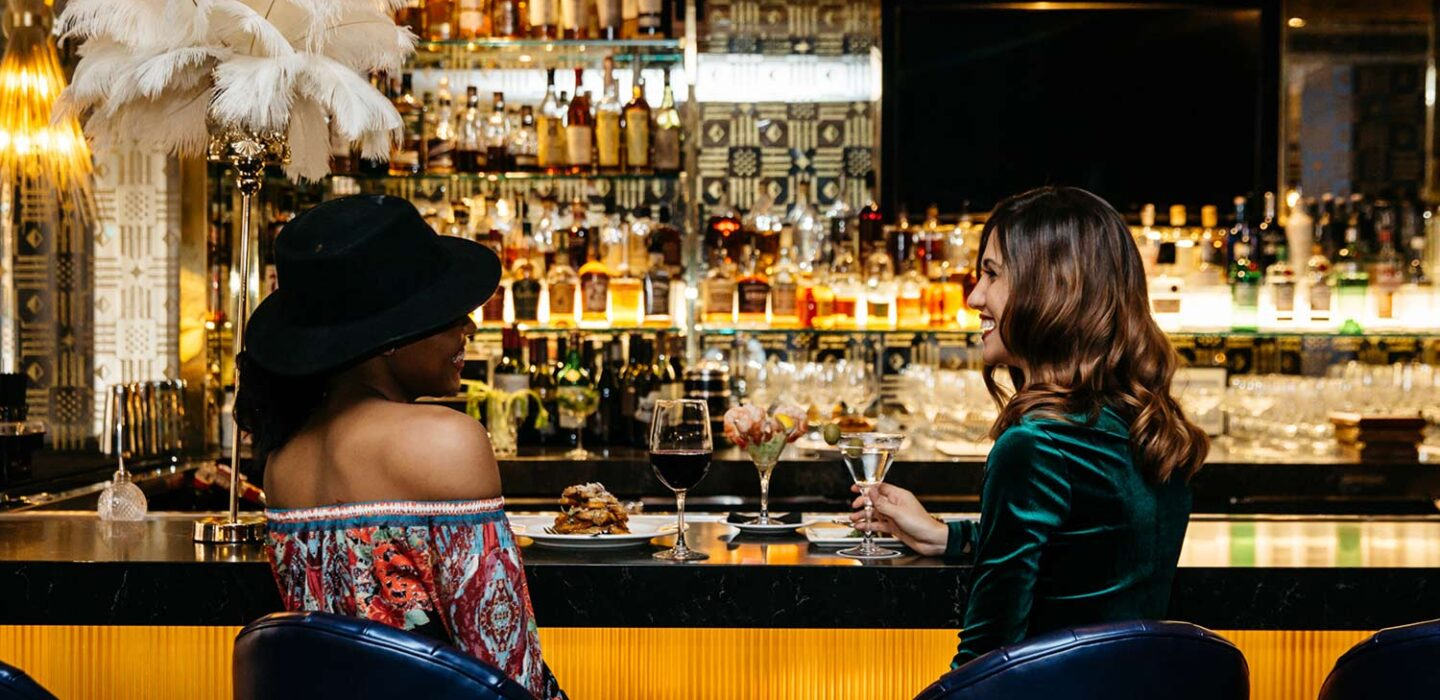 two women sitting at a bar smiling at each other with cocktails in hand