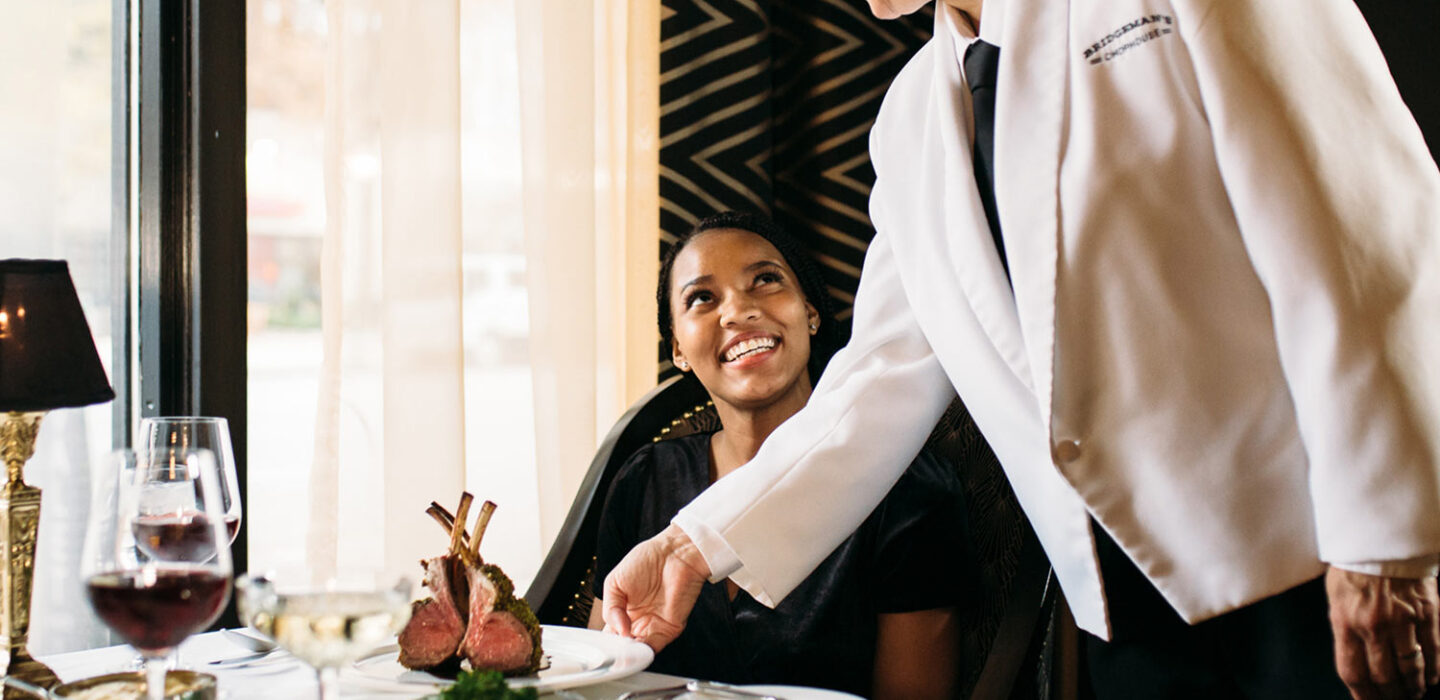 waitress handing a plate of meat to a smiling female guest