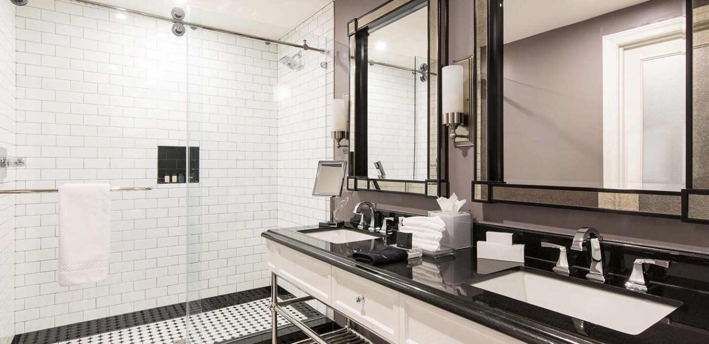black and white tiled bathroom with a single vanity and a walk in shower