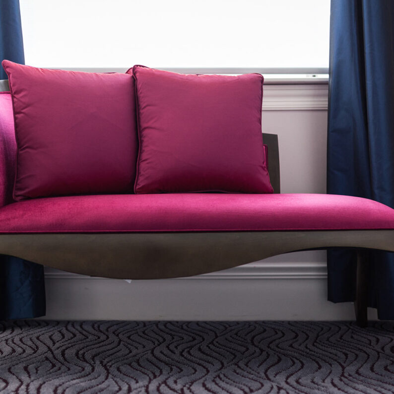 wooden day bed with pink cushions below a bright window with blue curtains