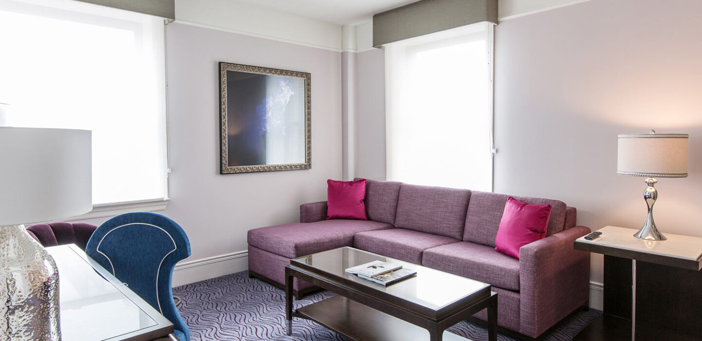 couch area with a rectangle table and lamp in front of a bright window