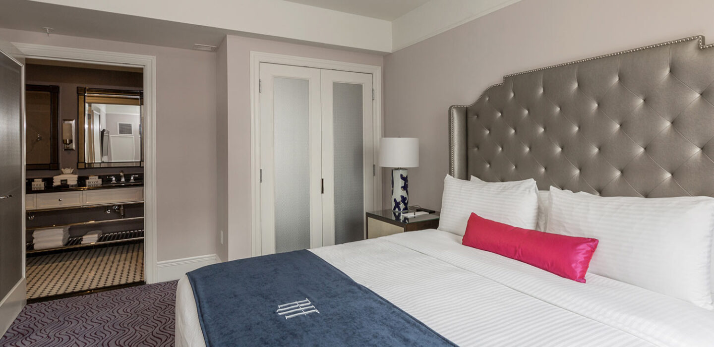 queen bed with a soft silver headboard and white linens next to a modern nightstand and a desk