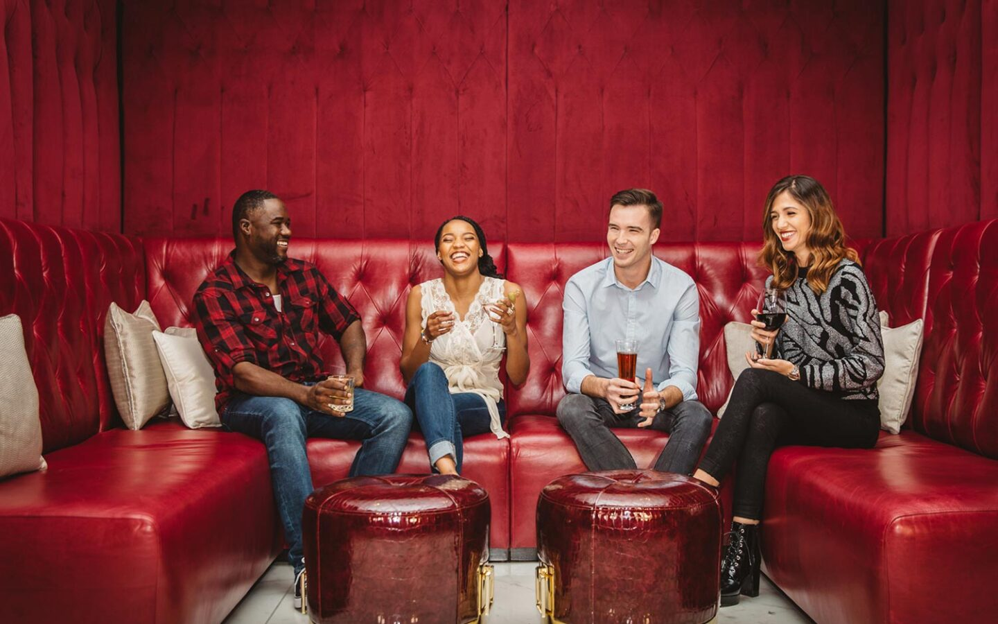 four people sitting on a red couch laughing