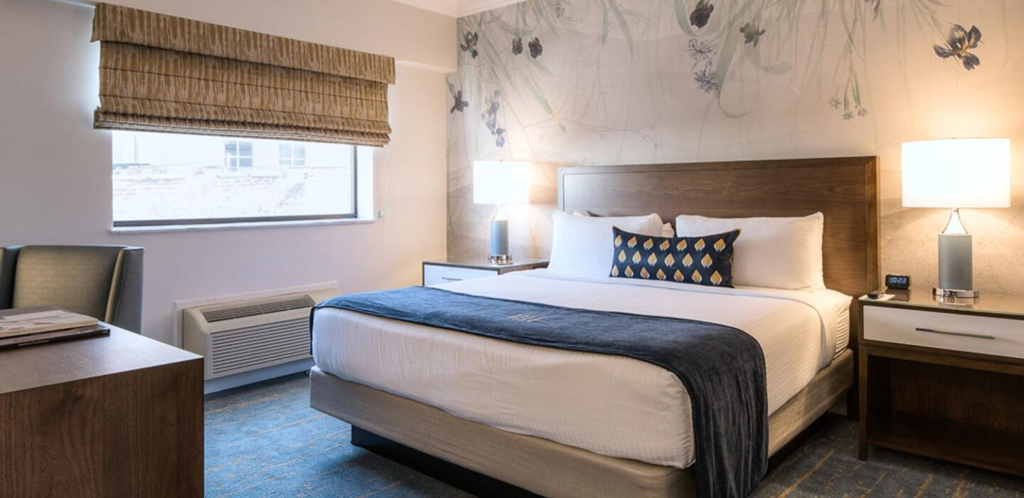 king bed with blue and white linens, two nightstands and a floral wallpaper behind it