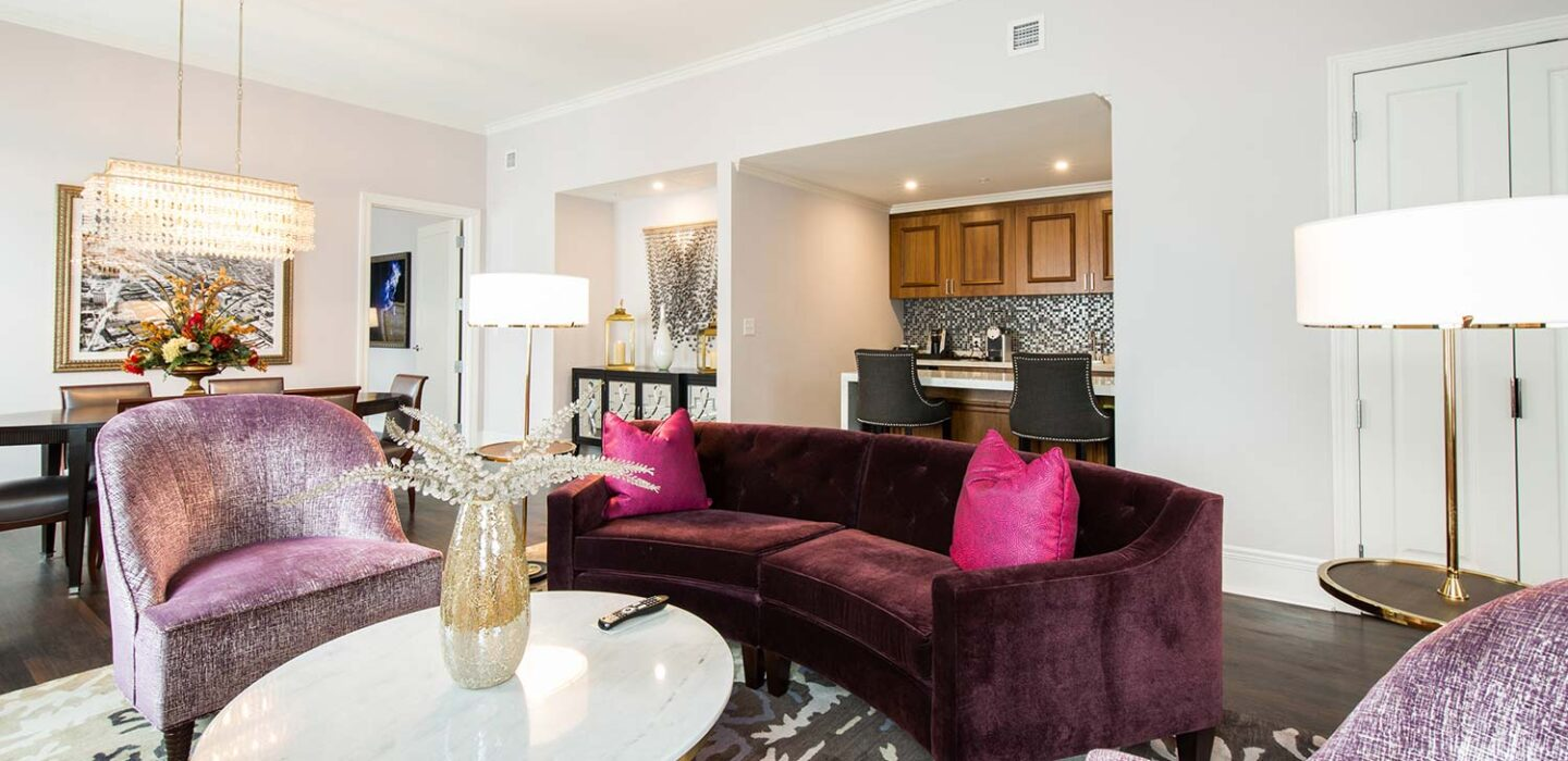 penthouse lounge room with purple suede chairs and a wet bar next to a dining table