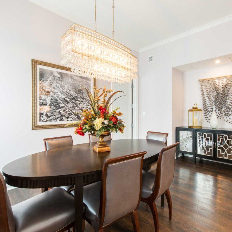 dining table and chairs under a large crystal light fixture in a penthouse