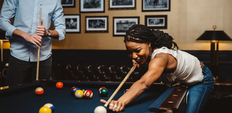 woman playing pool at a billiard