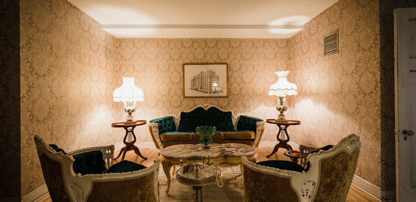 dated hotel room seating area with vintage couches and patterned wallpapered walls