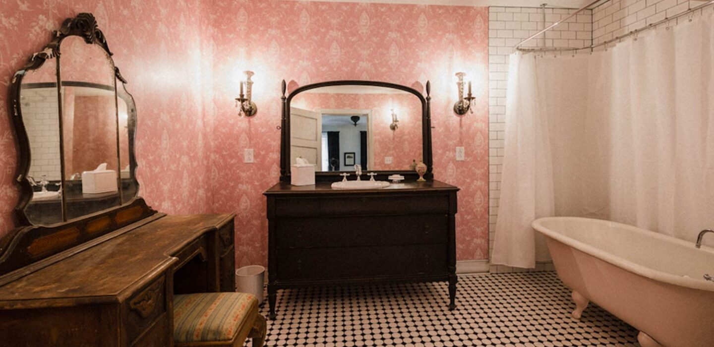 dated bathroom with a footed tub, wooden sink, and wooden vanity and mirror
