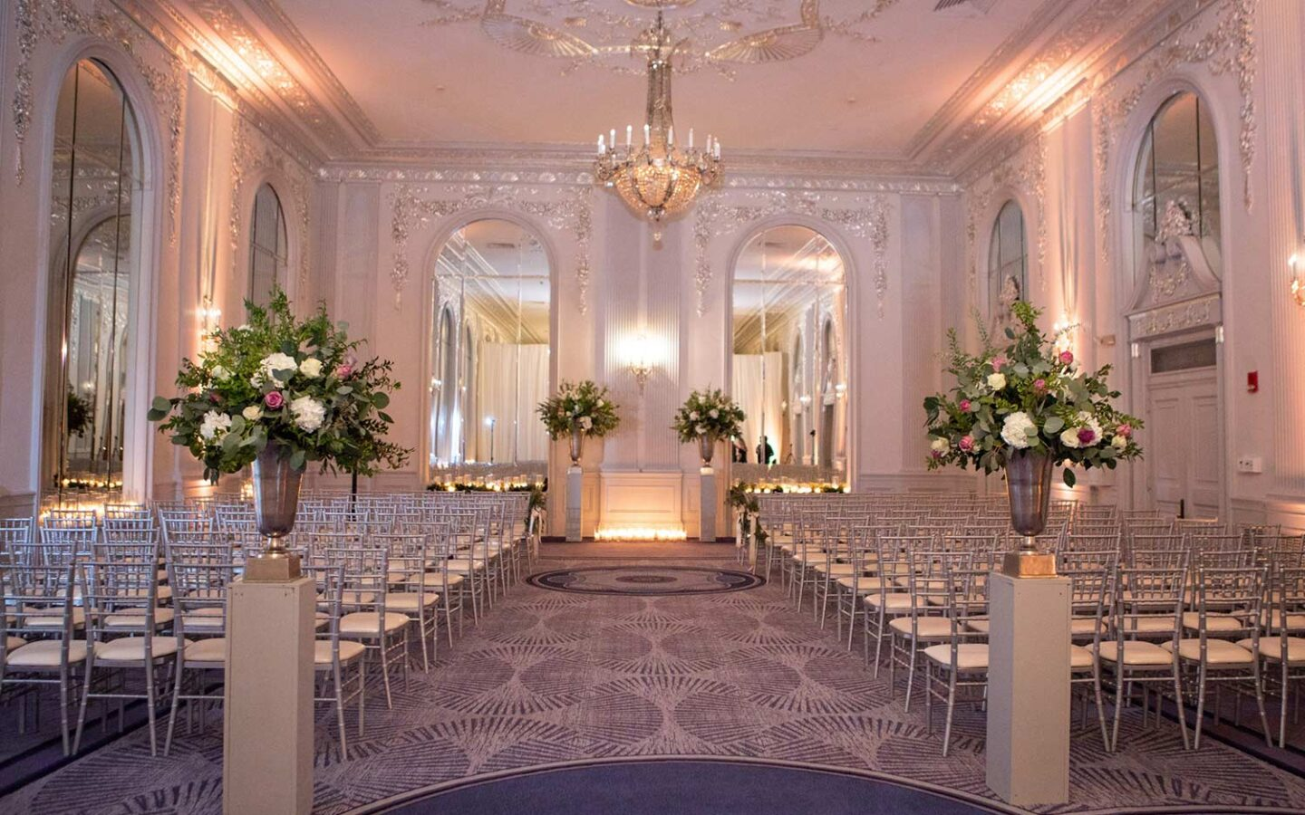 wedding space with rows of silver chairs, two floral arrangements, and a large crystal chandelier