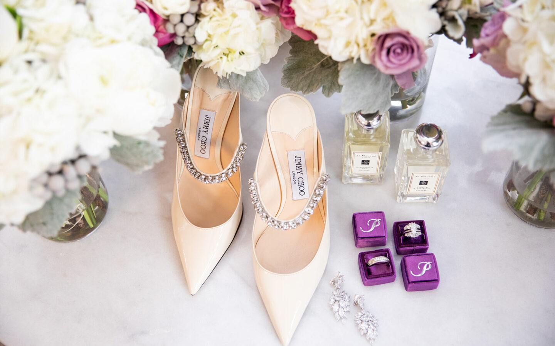 closeup of jimmy choo high heels next to wedding rings, earrings, and perfume