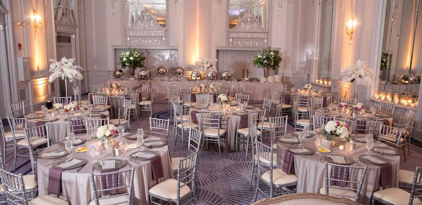 wedding venue room with tall ceilings, silver details on the walls, and silver tables and chairs