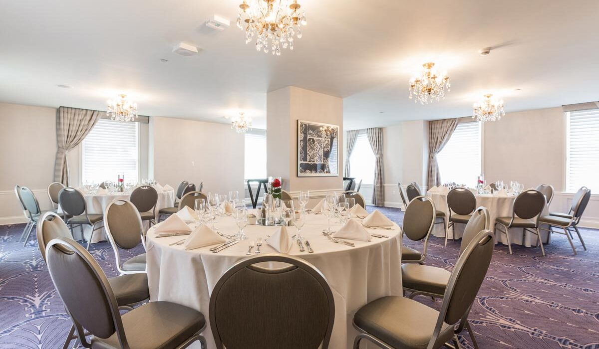event venue room with crystal chandeliers above round tables and chairs