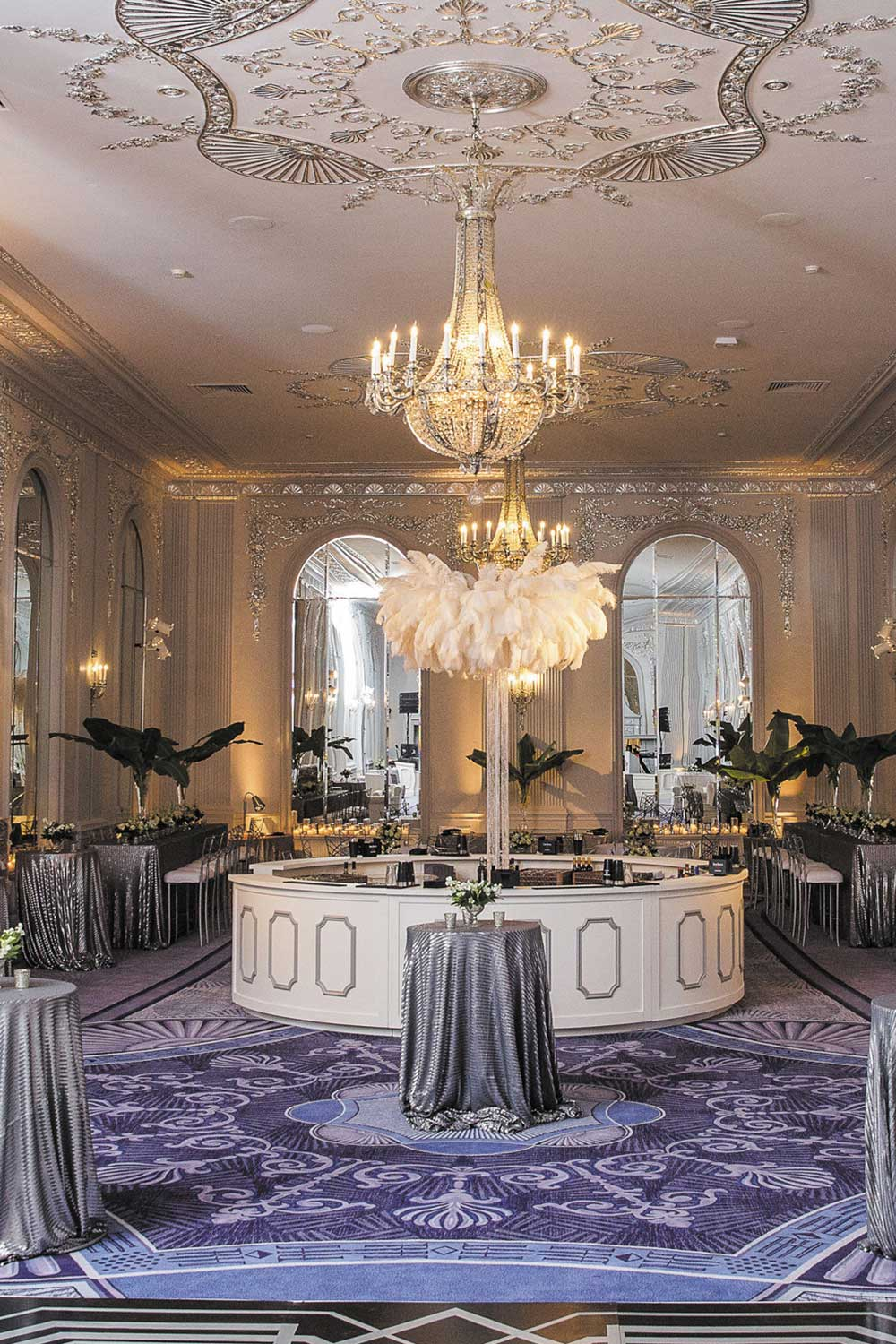 Wedding Venue room with silver wall designs and a large crystal chandelier