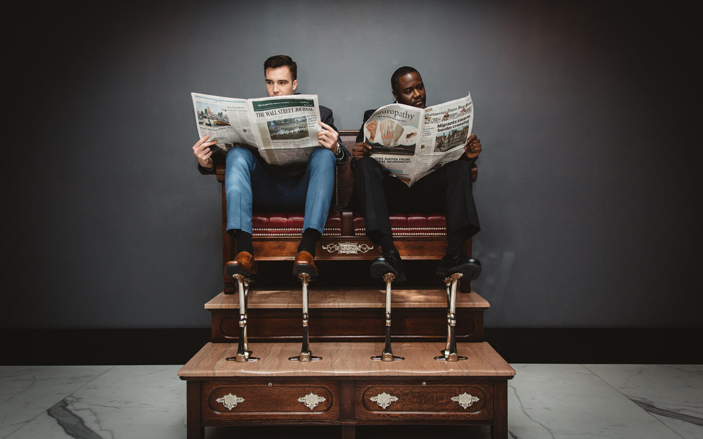 men on shoe shine chairs reading the newspaper
