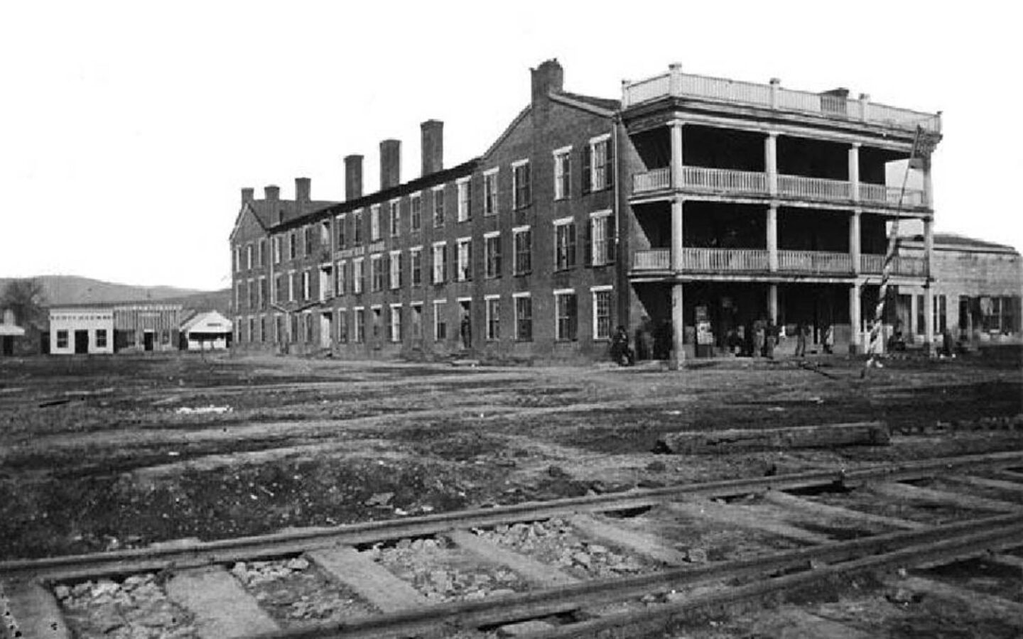historical black and white photo of a building on dirt land next to a train track
