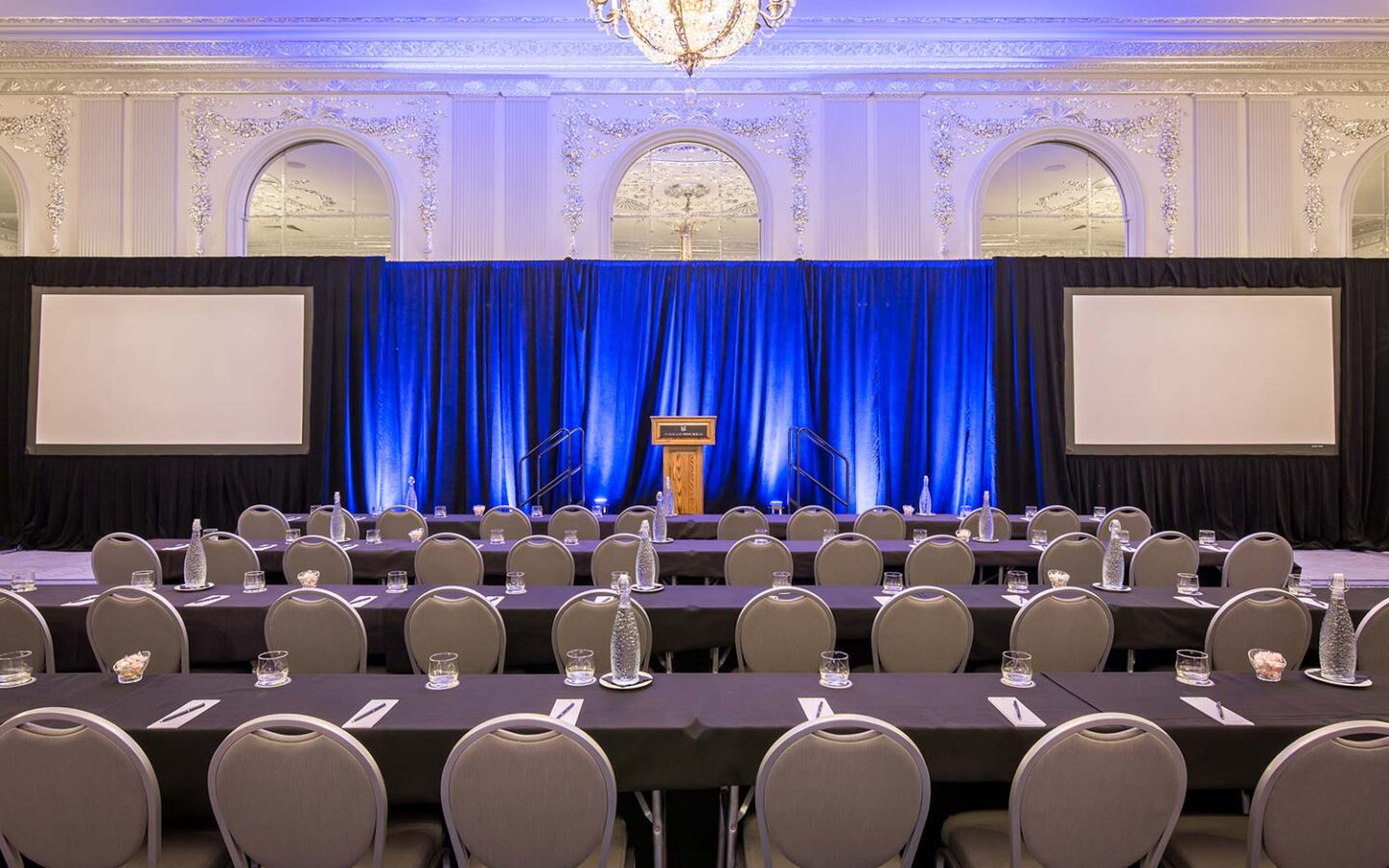 large ballroom event space with a stage and podium set up with rows of chairs in front of it