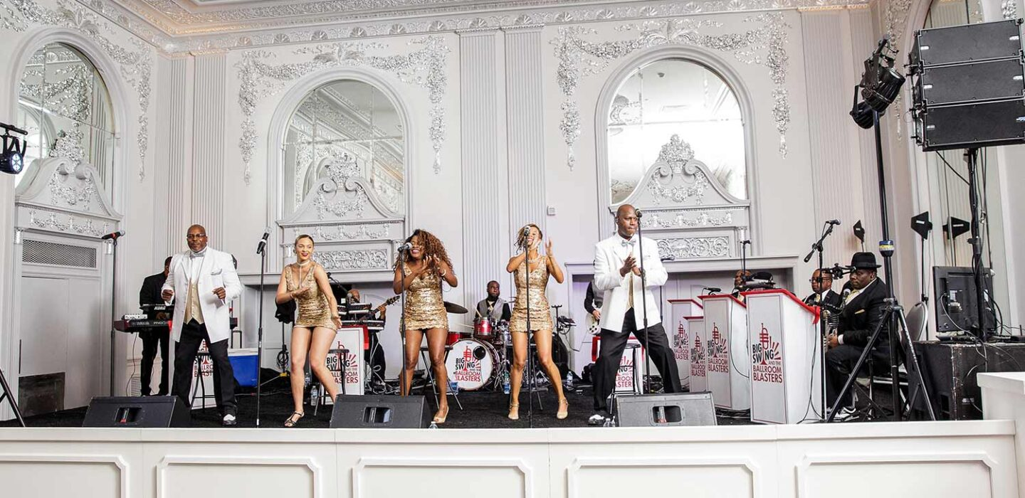 five performers and a band on stage singing and dancing in a ballroom