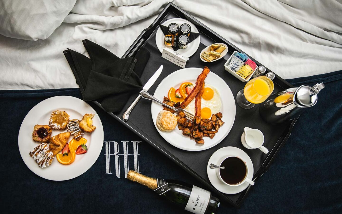 overhead view of a tray of breakfast foods, coffee, and orange juice on a bed