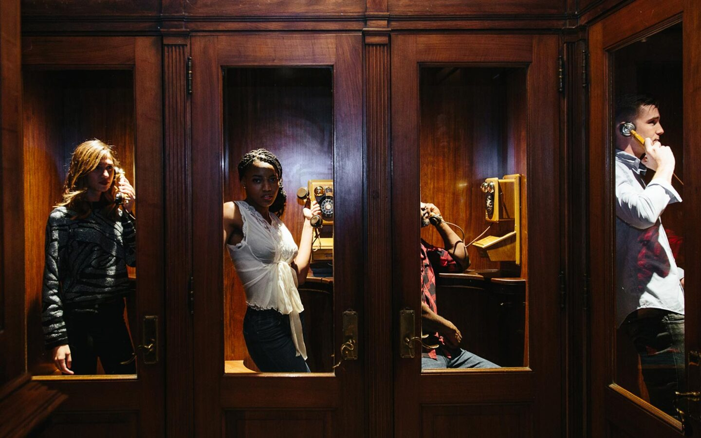 three people standing in dimly lit phone booths
