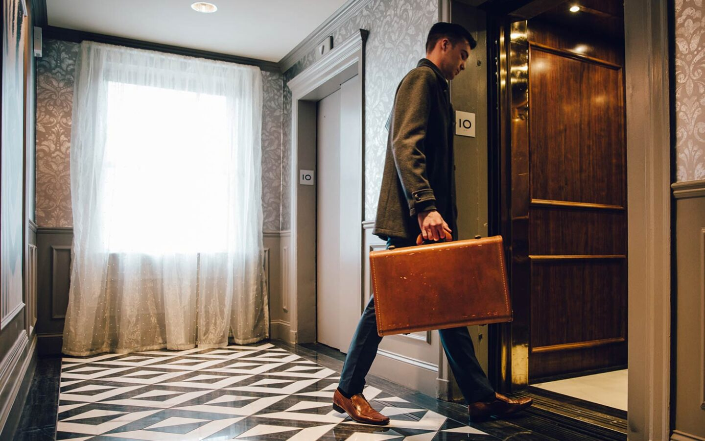 man holding a briefcase walking into an elevator