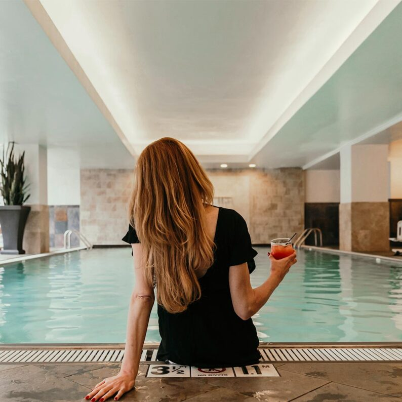 back of a woman who is holding a red cocktail on the edge of a pool