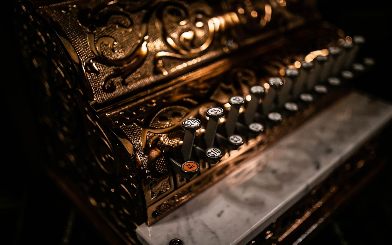 closeup of a gold vintage cash register