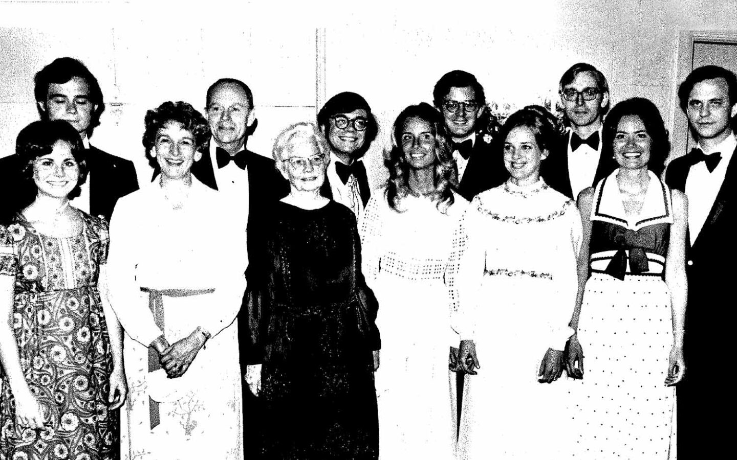 historical black and white photo of a group of people smiling at the camera